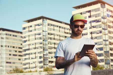 trucker: Serious young man wearing white plain t-shirt and red, yellow and black trucker hat looking at his tablet against city buildings and sky background