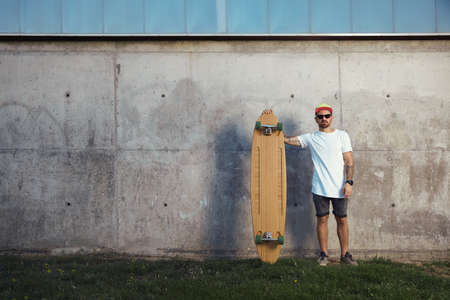 looking directly at camera: Serious looking surfer with beard, tattoos and sunglasses standing next to his longboard looking directly into camera