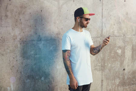 Young man in plain white t-shirt and baseball cap listening to music on his smartphone and looking at it against gray concrete wall background Stock Photo