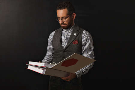 stringent: Serious bearded professor in plaid oxford shirt and tweed vest, wearing glasses reads educational plan in two big document folders for his student for next year in university