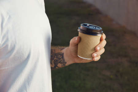 Closeup of a hand and chest of a white tattooed man wearing white unlabeled t-shirt holding a light brown paper coffee cup against background of green lawn.
