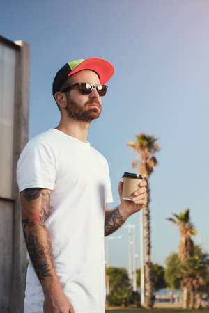 unlabeled: Young man with beard and tattoos in unlabeled white t-shirt with a coffee cup against blue sky and palm trees LANG_EVOIMAGES