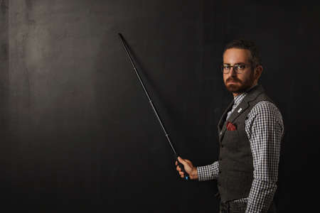 Serious bearded professor in plaid shirt and tweed vest, wearing glasses and looking condemn on camera, shows something on school black board with his pointer Фото со стока