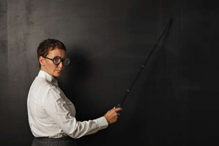 stringent: Angry teacher with pointer shows something on black chalk board , stays in left part of image