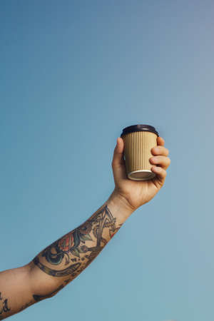 caffeine free: Tattooed white man holds a beige disposable coffee cup high against the clear blue sky LANG_EVOIMAGES