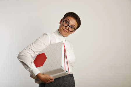Surprised funny woman teacher looks at camera inquiringly and holds two big document folders with new educational plan