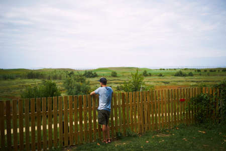 trucker: Full body shot of a young man in shorts, light blue t-shirt and trucker hat leaning on a wooden fence and looking at a meadow and cloudy sky LANG_EVOIMAGES
