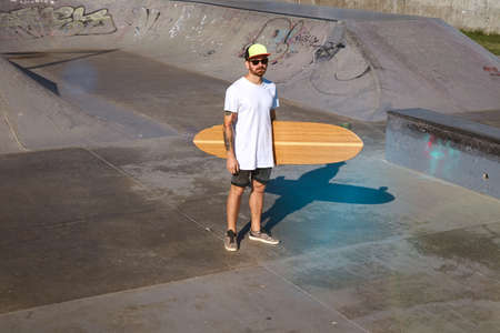 trucker: Young attractive tattooed skater in trucker cap stands in unlabeled blank white t-shitrt with his wooden longboard in hand in center of concrete pool in skatepark, top view LANG_EVOIMAGES