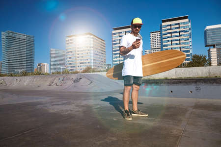 unlabeled: Young attractive bearded man with tattooes wearing unlabeled white t-shirt looks at his smartphone ,holds big bamboo longboard in center of concrete pool in urban skatepark