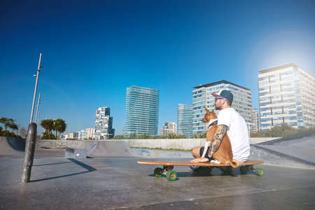 Surfer in trucker hat sits on his longboard skate hugging his basenji dog in empty morning skate park pool Sun flare mirrored from building