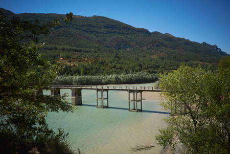 bridge over water: Green hills, shallow bay and a pedestrian bridge over water on a hot summer day LANG_EVOIMAGES