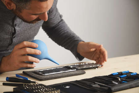 Professional is working in his lab to repair and clean smart phone using syringe to blow out all dust from device