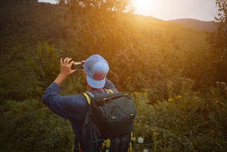 mochila de viaje: Hombre joven con una gorra de béisbol mochila y tomar una foto de los árboles y las colinas mientras que emigra al atardecer LANG_EVOIMAGES