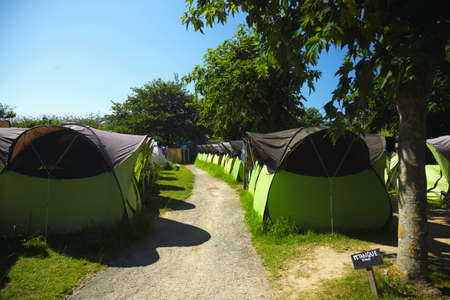 Rows of identical light green and black tents with a dirt path between them under trees and blue sky in surf camping LANG_EVOIMAGES