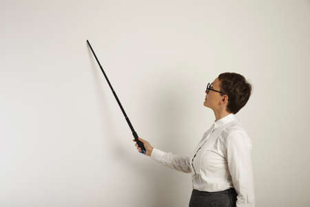 rigorous: Focused young female teacher in conservative clothing teaching a lesson at a whiteboard holding a black plastic pointer