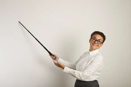 stringent: Conservatively dressed caucasian female teacher in ugly round glasses holding a pointer to an empty whiteboard and smiling unpleasantly LANG_EVOIMAGES