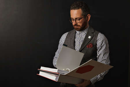 facilitator: Hip young serious teacher in checkered shirt and tweed vest standing at a blank blackboard and reading from a thick bright red and white binder