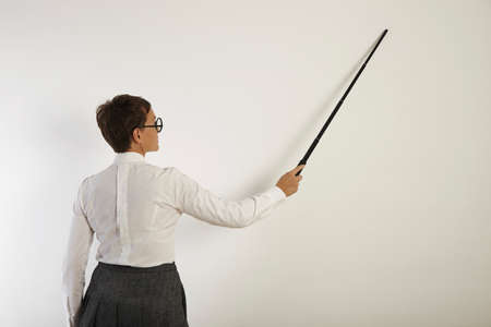 stringent: Back shot of a serious looking white female teacher in blouse, skirt and glasses pointing at a white wall with a black pointer