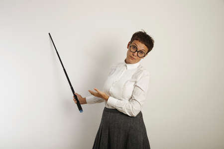 conservative: Bored and exhausted female teacher in conservative blouse and skirt points at a whiteboard with a black pointer