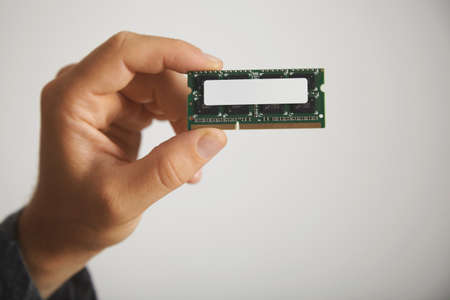 unlabeled: Unlabeled memory chip in a mans hand against a white wall background