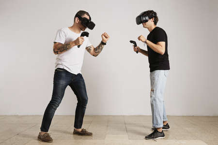 unlabeled: A man in white unlabeled t-shirt with bear and tattoos and a man in black unlabeled t-shirt wearing VR headsets fight in a room with white walls.
