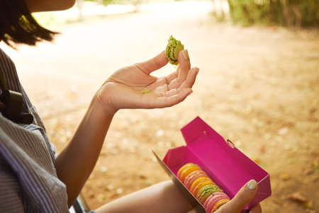 dark haired: Dark haired young woman eating crumbling pistachio green macaroon from a pink cardboard box sitting in a park, close up LANG_EVOIMAGES