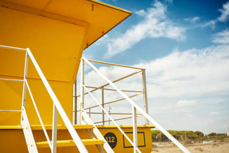 Close up shot of a beautiful yellow lifeguard post against the background of blue sky and some white clouds LANG_EVOIMAGES