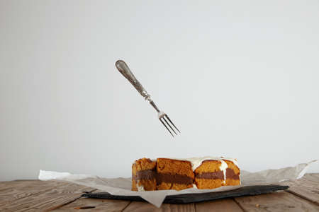 dessert fork: Vintage silver dessert fork flying into a delicious yellow-brown cake with cream and chocolate on a wooden table LANG_EVOIMAGES
