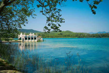 rowboats: View of a stunning old boathouse on a beautiful blue lake surrounded by green hills on a quiet clear day