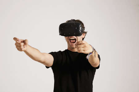 unlabeled: Emotional young gamer in VR headset and black unlabeled t-shirt screams while playing a game