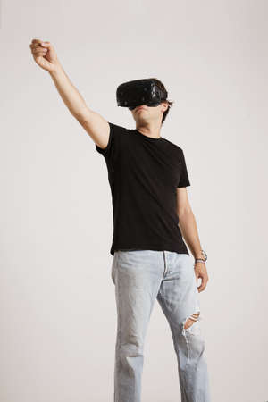 unlabeled: Full body shot of a man in torn jeans and unlabeled black t-shirt wearing VR headset holding something high up isolated on white LANG_EVOIMAGES