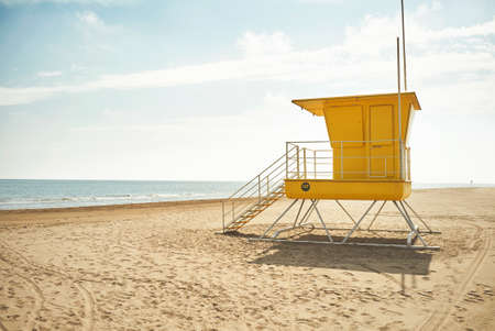 Yellow lifeguard post on an empty sandy beach with the background of blue sky with clouds and the sea LANG_EVOIMAGES