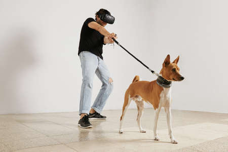 unlabeled: A young gamer in VR headset and black unlabeled t-shirt pulling a leash on a brown and white basenji dog against a white wall background. LANG_EVOIMAGES