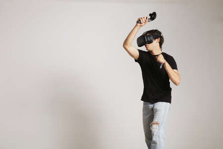 Young man in blank black t-shirt gaming golf or tennis in VR headset hitting someting isolated on white Standard-Bild