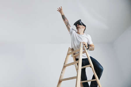 unlabeled: A bearded and tattooed young man in an unlabeled white t-shirt and VR glasses standing on a ladder and reaching up for something