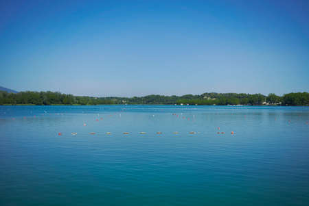 greenish blue: Lines of buoys marking rowing lanes on a peaceful greenish blue lake under a quiet sunny sky