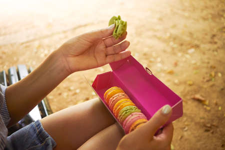 Close up shot of hands and knees of a young woman eating a light green macaron out of a full colorful box sitting outside