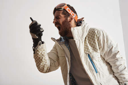 Man in snowboard gear with googles on head screaming into walkie talkie Stock Photo