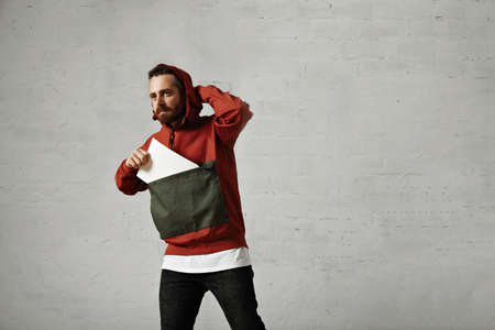 anorak: Handsome young man adjusts the hood of his stylish anorak and takes a blank piece of paper out of its front pocket