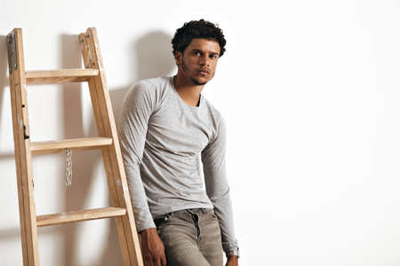 stepladder: Serious sad muscular African American model in heather grey longsleeve cotton t-shirt and jeans leaning on a white wall next to a wooden stepladder