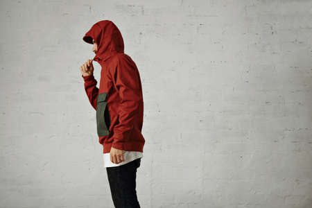 anorak: A serious looking young man zips up his fashionable red and grey anorak, shot from the side isolated on white