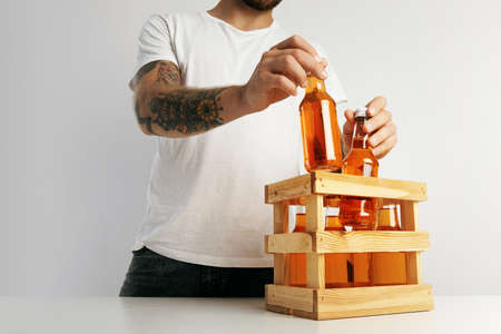A hipster in plain white t-shirt packing bottles of orange lemonades into a wooden box on white table Stock Photo