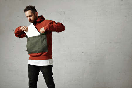 anorak: Hip bearded young man putting a blank sheet of paper into the huge front pocket of his red and gray anorak against white wall background LANG_EVOIMAGES