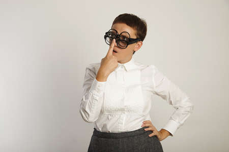 conservative: Crazy looking teacher in conservative white blouse adjusting three pairs of black glasses lost in thought isolated on white