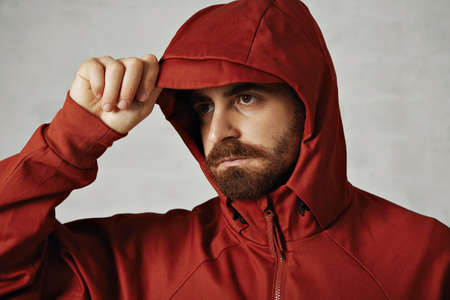anorak: Close up of a man with beard adjusting the hood of his red anorak isolated on white LANG_EVOIMAGES