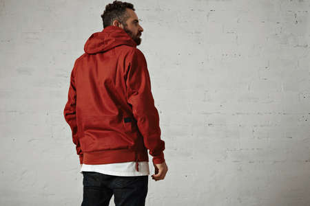 anorak: Back shot of a stylish bearded guy wearing a brick red anorak, black jeans and white t-shirt isolated on white