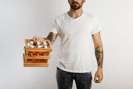sixpack: A young fit model with tattoos and beard holding a sixpack of unlabeled orange drinks isolated on white