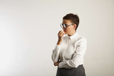 conservative: Teacher in conservative white and grey outfit and round black glasses deep in thought isolated on white