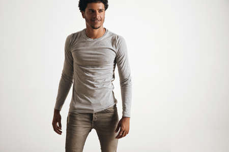 wears: Sexy fitted latino male walking wears blank unlabeled grey logsleeve and stressed jeans, isolated on white LANG_EVOIMAGES