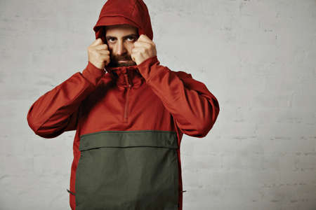 anorak: Serious looking bearded hipster in a red and grey parka adjusting his hood against grey wall background